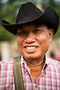 06 APRIL 2013 - SANPATONG, CHIANG MAI, THAILAND: A Thai farmer with an American style cowboy hat at the Sanpatong buffalo market in northern Thailand. The buffalo market in Sanpatong (also spelled San Patong) started as a weekly gathering of farmers and traders buying and selling water buffalo, the iconic beast of burden in Southeast Asia, more than 60 years ago and has grown into one of the largest weekend markets in northern Thailand. Buffalo and cattle are still a main focus of the market, but traders also buy and sell fighting cocks, food, clothes, home brew and patent medicines.         PHOTO BY JACK KURTZ