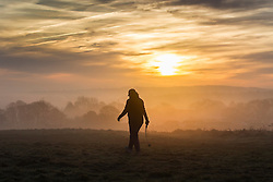 © Licensed to London News Pictures. 12/12/2016. Baildon UK. A dog walker walks in the fog on Baildon moor this morning at sunrise in Yorkshire. Photo credit: Andrew McCaren/LNP