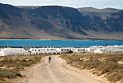 Cyclist dirt track leading to Caleta de Sebo village on Graciosa island, Lanzarote, Canary Islands, Spain