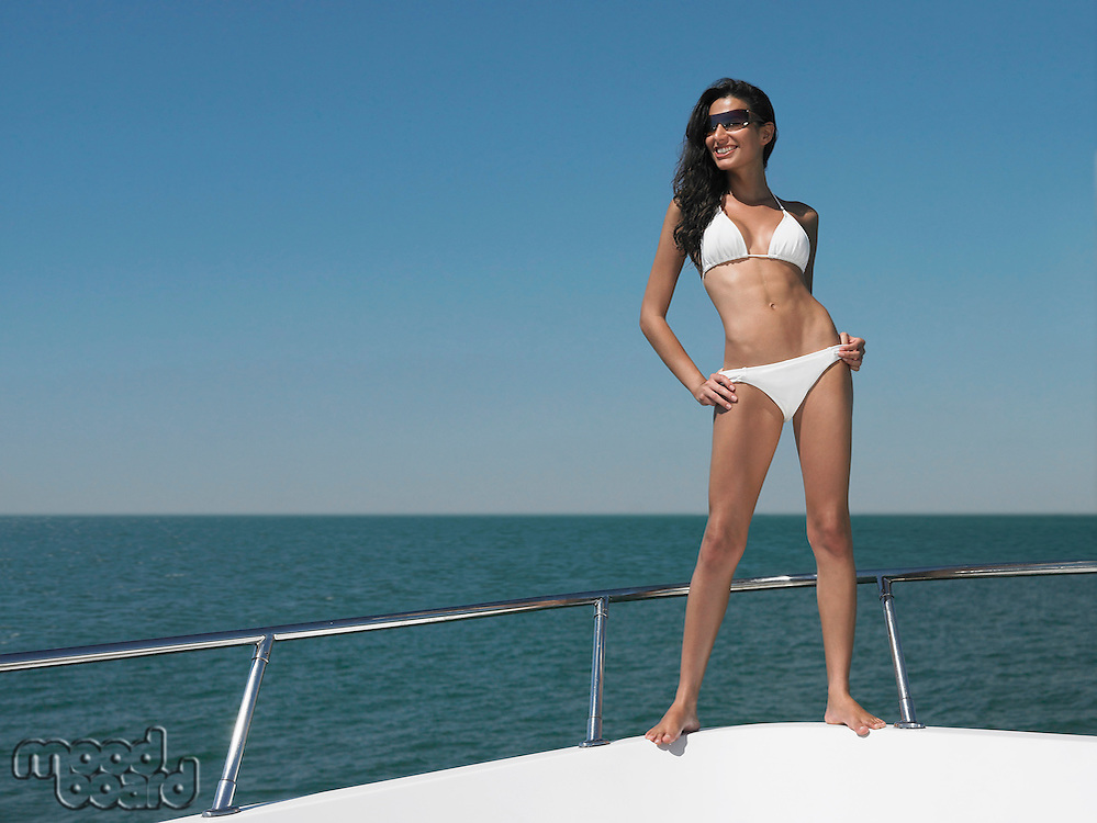 Young woman in bikini standing on bow of yacht portrait