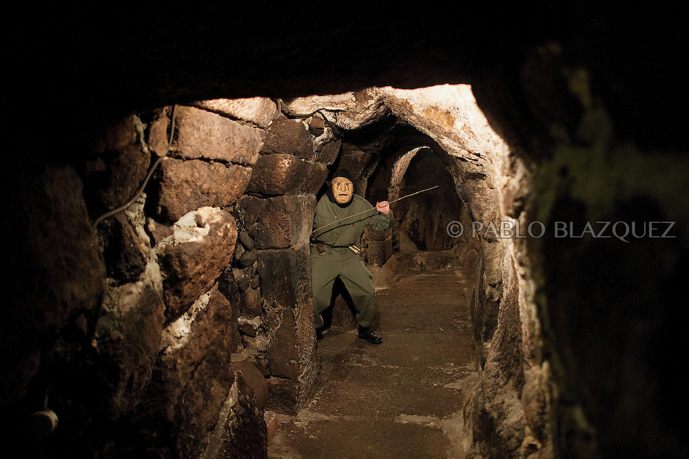 A Machurrero from Pedro Bernardo poses for pictures inside a cave before walking the streets during Carnival on February 6, 2016 in Pedro Bernardo, in Avila province, Spain. The origins of this pagan festival are unknown. The Machurreros wear wood masks, a military dress, black handkerchief, cowbells, and hold wicker stick. The festival disappeared after Dictator Franco forbid carnival festivals in 1937, but it was recently recovered. Before disappearing, male villagers after the military service, used to dress as Machurreros as they run along the streets scaring children and adults with their wicker stick to bring fertility to the land and expel the evil spirits. (© Pablo Blazquez)