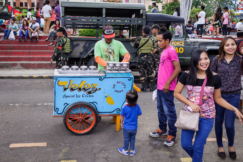 Davao City, Mindanao, Philippines - JUNE 18: A street vendor sells ice cream while members of the Davao Task Force Army are seen on stand by at Quezon Park near the City Hall.  Security in the city is tight since President Duterte implemented a Martial Law for 60 days in Mindanao due to the heavy fighting in Malawi 250km away.