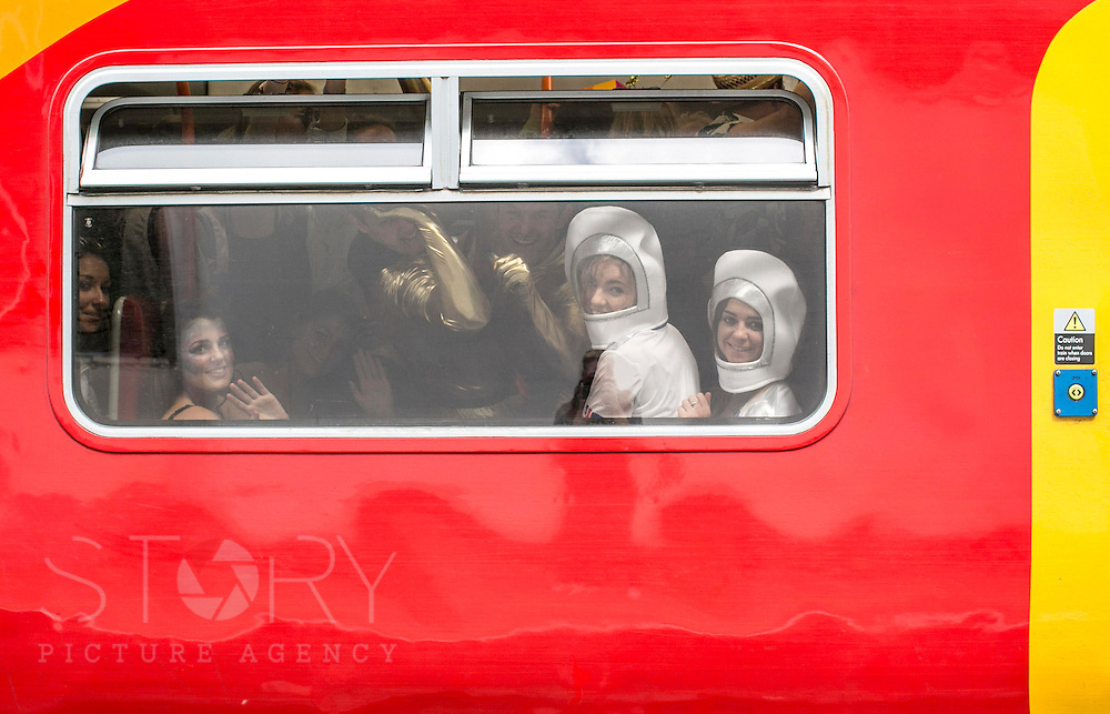 "UNITED KINGDOM, London: 16 May 2015 Rugby fans travel to Twickenham on the train for the Marriott London Sevens Rugby tournament. More than 113,000 fans, most of them in fancy dress, will ascend onto Twickenham for the sporting entertainment. This years fancy dress theme was ""Space"". Rick Findler / Story Picture Agency"