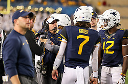 Nov 4, 2017; Morgantown, WV, USA; West Virginia Mountaineers head coach Dana Holgorsen talks with West Virginia Mountaineers quarterback Will Grier (7) and West Virginia Mountaineers wide receiver Gary Jennings (12) during the fourth quarter against the Iowa State Cyclones at Milan Puskar Stadium. Mandatory Credit: Ben Queen-USA TODAY Sports