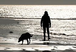 © Licensed to London News Pictures. 26/02/2019. Selsey, UK. A woman walks her dog on the beach at Selsey, West Sussex at first light ahead of another day of unseasonably high winter temperatures. Photo credit: Peter Macdiarmid/LNP