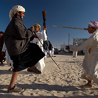 Oman, Ra's al-Hadd. February 07/2008.<br /><br />Two boys at an Omani wedding play-fighting with swords in a game that attempts to nick the hand of one's opponent while avoiding the same in return.
