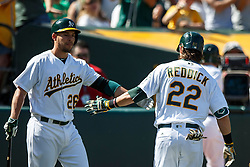 OAKLAND, CA - APRIL 17:  Josh Reddick #22 of the Oakland Athletics is congratulated by Danny Valencia #26 after hitting a sacrifice fly for an RBI against the Kansas City Royals during the eighth inning at the Oakland Coliseum on April 17, 2016 in Oakland, California.  The Oakland Athletics defeated the Kansas City Royals 3-2. (Photo by Jason O. Watson/Getty Images) *** Local Caption *** Josh Reddick; Danny Valencia