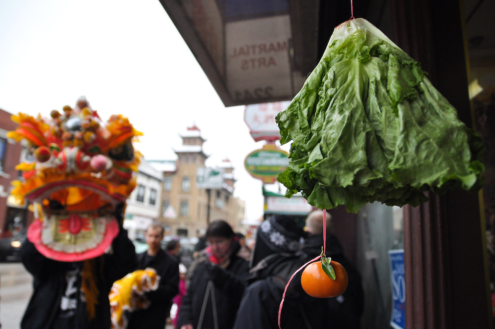 "Vegetables and fruit are  often put outside of participating businesses to attract lion dancers. Hanging the vegetables or placing them on a chair challenges the dancers to creatively reach and ""eat"" the vegetables or fruit, and therefore winning the reward of the red envelope containing money. Chinese New Year, Chinatown, Chicago, February 6th, 2011"