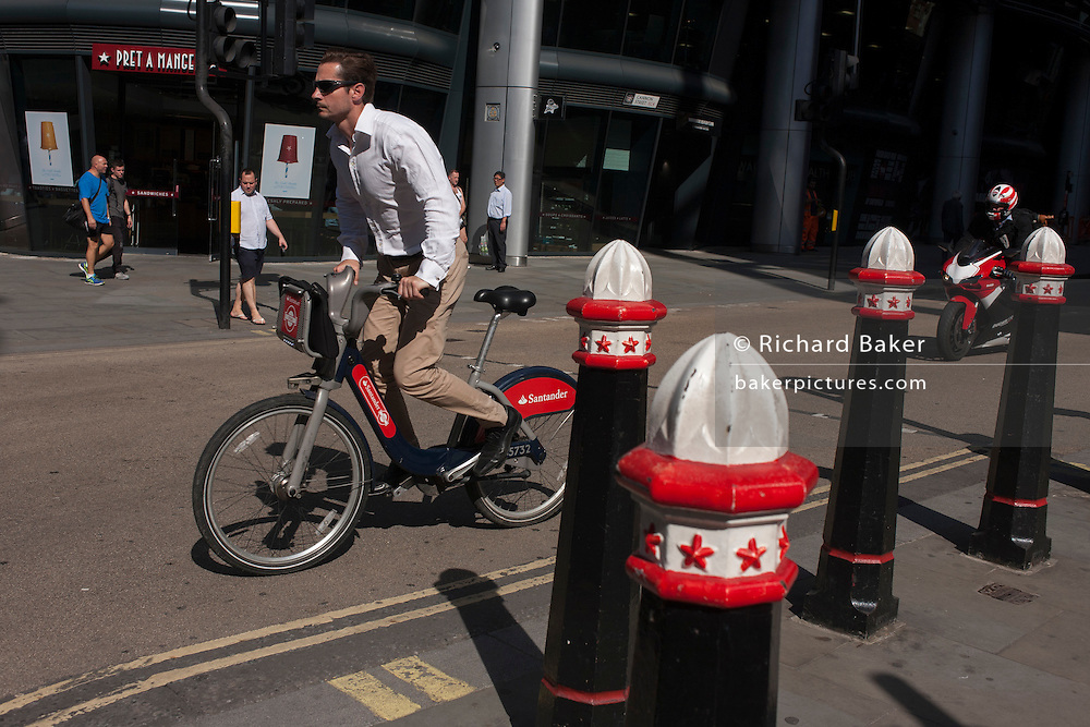 A Santander cyclist pedals along Cannon Street in the City of London, UK.