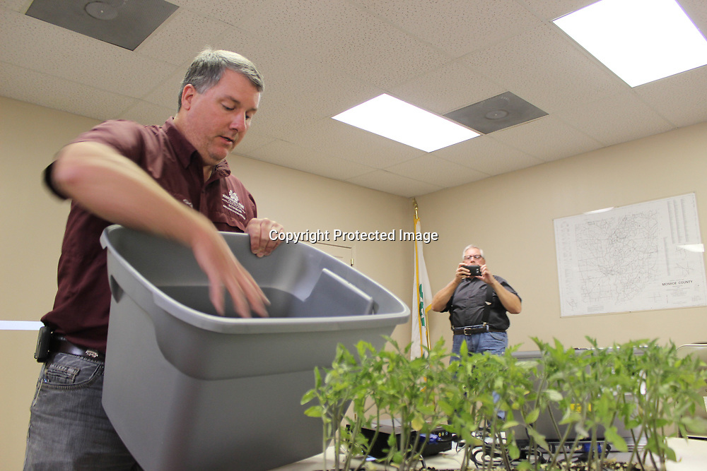 RAY VAN DUSEN/BUY AT PHOTOS.MONROECOUNTYJOURNAL.COM<br /> Monroe County Extension Service Agent Randall Nevins, left, explains how to make a self-watering container for vegetables during a recent tomato workshop as keynote speaker Stanley Wise takes a photograph.