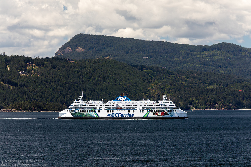 BC Ferries vessel Coastal Celebration (built in 2007) navigates Swanson Channel on the way to Tsawwassen from Victoria (Swartz Bay) .  Photographed from Otter Bay at Pender Island, British Columbia, Canada. Salt Spring Island (and Mount Maxwell/Baynes Peak) is in the background.