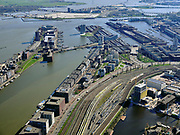 "Nederland, Noord-Holland, Amsterdam; 23-03-2020; Piet Heinkade met emplacement van de NS (Rietlanden). Oostelijke eilanden met IJhaven en Veemkade, Dijksgracht (rechts).<br /> Door de Coronacrisis is er weinig verkeer en omdat de NS een speciale basisdienstregeling ingevoerd, zijn veel treinen 'geparkeerd' op opstelsporen. <br /> Piet Heinkade with railway yard of the NS (Rietlanden). Eastern islands with IJhaven and Veemkade, Dijksgracht (right).<br /> Due to the Corona crisis, there is little traffic and because the NS has introduced a special basic timetable, many trains are ""parked"" on Railway yard.<br /> <br /> luchtfoto (toeslag op standaard tarieven);<br /> aerial photo (additional fee required)<br /> copyright © 2020 foto/photo Siebe Swart"
