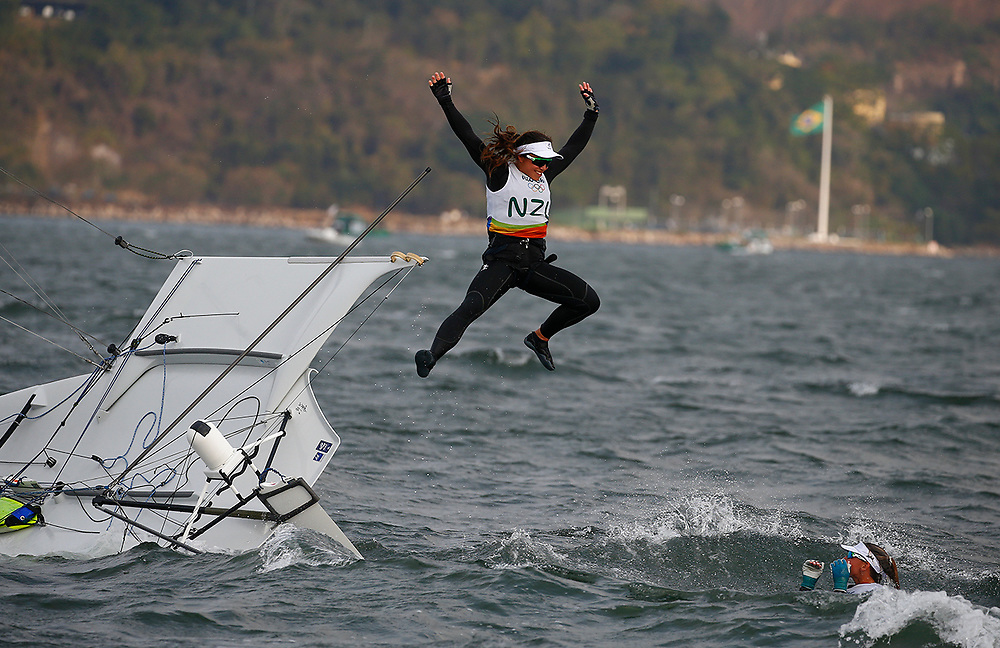 Alexandra Maloney and Molly Meech from New Zealand react by jumping off their boat after winning the Silver medal in the 49er FX Women's class medal race of the Rio 2016 Olympic Games Sailing events in Rio de Janeiro, Brazil, 18 August 2016.