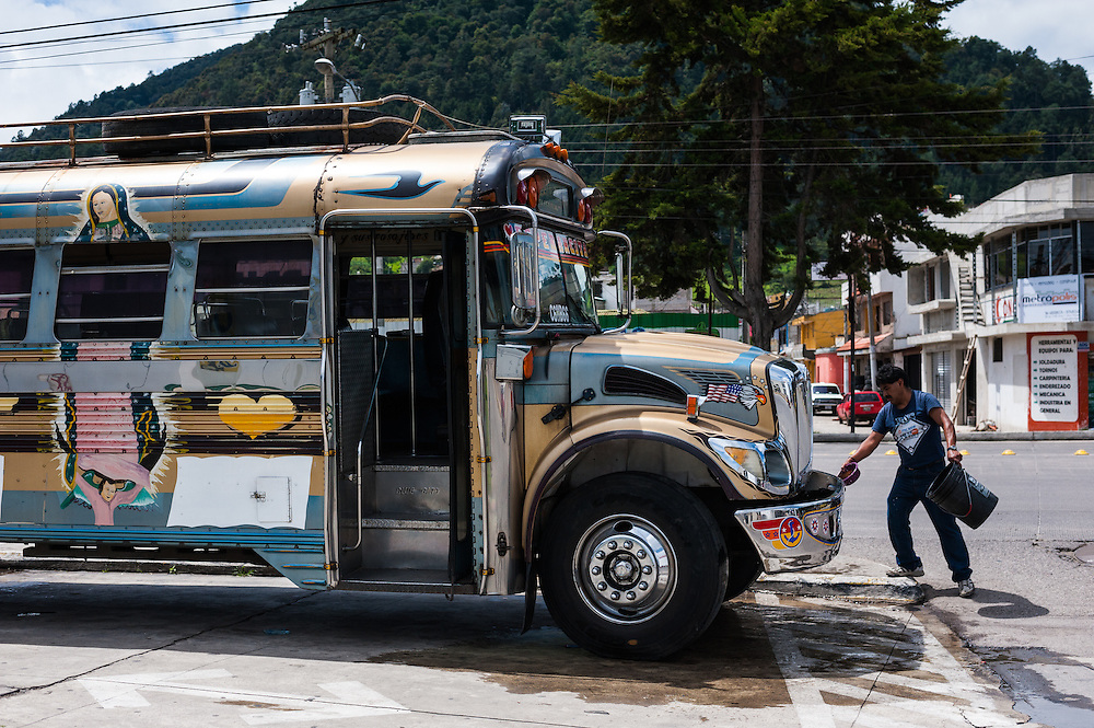 A man washes his bus alongside Avenida La Independencia in Xela.