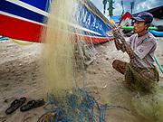 03 AUGUST 2017 - KUTA, BALI, INDONESIA: A local fishermen repairs his nets next to his outrigger canoe on Jimbrana Beach in Kuta. The beach is close to the airport and a short drive from other beaches in southeast Bali. Jimbrana was originally a fishing village with a busy local market. About 25 years ago, developers started building restaurants and hotels along the beach and land prices are rising. The new emphasis on tourism is changing the nature of the area but the fishermen are still busy very early in the morning.     PHOTO BY JACK KURTZ