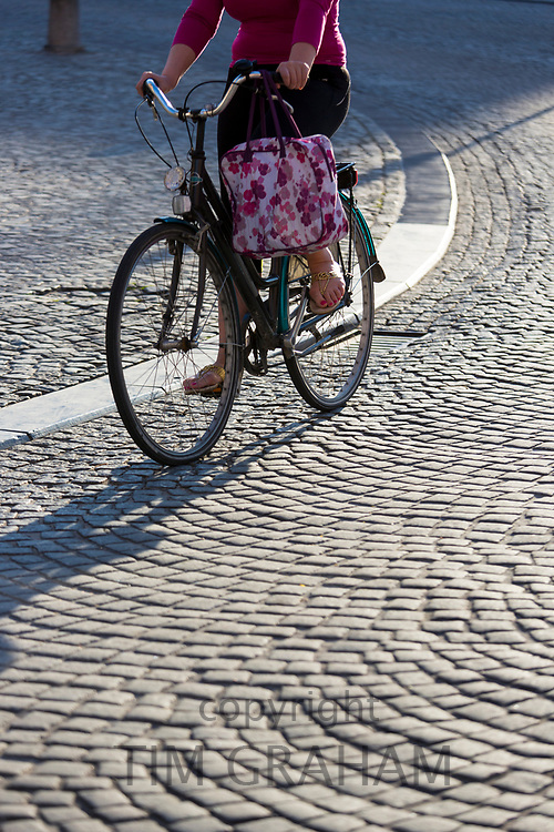 Woman cyclist wearing a skirt while cycling an old-fashioned bicycle on cobble stones in Bruges, Belgium