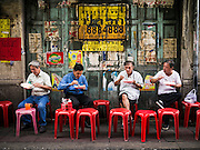 10 SEPTEMBER 2013 - BANGKOK, THAILAND:    Men eat curry at a street side curry stand in the Chinatown section of Bangkok. Thailand in general, and Bangkok in particular, has a vibrant tradition of street food and eating on the run. In recent years, Bangkok's street food has become something of an international landmark and is being written about in glossy travel magazines and in the pages of the New York Times.     PHOTO BY JACK KURTZ