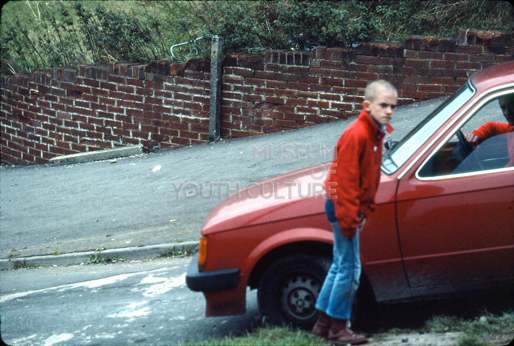 Neville by red car. Hawthorne Road, High Wycombe, UK. 1970s.