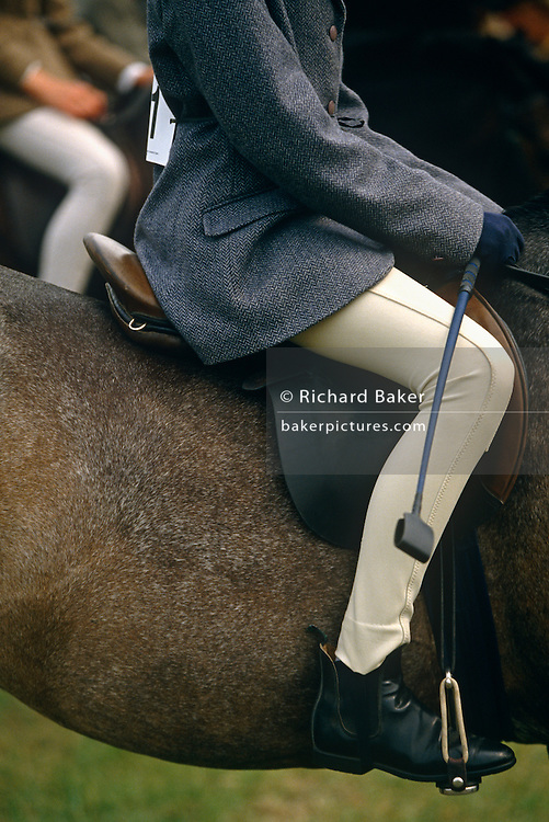 "The legs of two young girls sit astride their beloved ponies at a gymkhana in Cheltenham, Gloucestershire. Wearing a smart herringbone patterned jacket, regulation jodhpurs, short polished boots and holding a crop to encourage the horse to perform a series of trick and races, the rider nearest the viewer sits calmly awaiting the next event. The word gymkhana is an Indian Raj term that referred to a place where sporting events took place to test the skill of the competitors. In the UK and east coast of the US, the term gymkhana now almost always refers to an equestrian event for riders on horses, often with the emphasis on children's participation (such as those organised here by the Pony Club). Gymkhana classes include timed speed events such as barrel racing, keyhole, keg race (also known as ""down and back""), flag race, and pole bending."