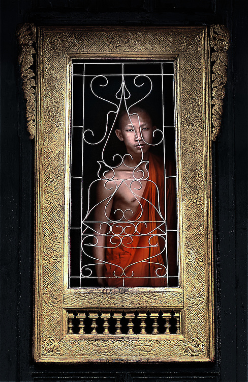 A novice monk at a window in Wat Hua Xiang, Luang Prabang, Laos.