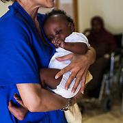 bambino di qualche mese in braccio ad un'infermiera dell'ospedale di Lampedusa. E' stato ricoverato con la madre subito dopo lo sbarco.