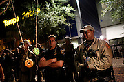 A protester holds up a donut to a law enforcement officer to try to get him to smile in Lykes Gaslight Square Park where demonstrators  spoke out against police brutality during the 2012 Republican National Convention on August 29, 2012 Tampa, Fla.