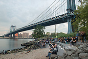 People sit on steps at Brooklyn Bridge Park under the Manhattan Bridge, a suspension bridge that spans the East River and connects Brooklyn with Manhattan, NYC.