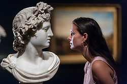 "© Licensed to London News Pictures. 29/06/2018. LONDON, UK. A staff member views ""Bust of the Apollo Belvedere"" (Est. £20-30k).  Preview of Old Masters, British, Treasures, Sculptures and Ancient works at Sotheby's New Bond Street to be offered for sale on 3 and 4 July 2018.  Photo credit: Stephen Chung/LNP"