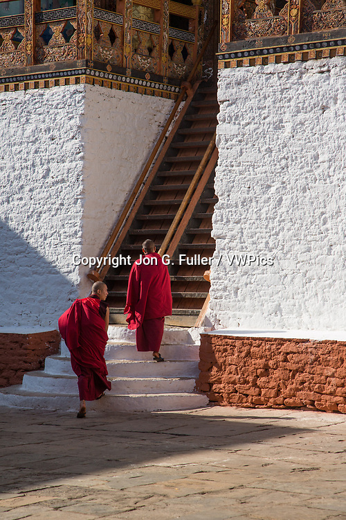 Two monks climb the steep stairs up to the Buddhist temple in the Punakha Dzong, Punakha, Bhutan.