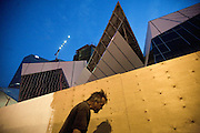 """A man walks past a building site on the """"Strip"""" in Las Vegas, Nevada."""