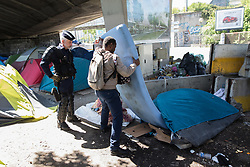 © Licensed to London News Pictures . 09/05/2017. Paris, France . A man picks through the contents of a tent , watched on by a police officer , at the scene where French police have cleared approximately 1000 people from an ad hoc roadside camp under roadways along a central reservation , in which migrants were living , in Porte de la Chapelle in North Paris , this morning (9th May 2017) . Photo credit: Joel Goodman/LNP