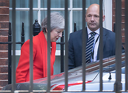 © Licensed to London News Pictures. 24/05/2019. London, UK. A close protection officer (R) looks on as Prime Minister Theresa May leaves Downing Street by the back door. Mrs May has announced that she is standing down next month. Photo credit: Peter Macdiarmid/LNP