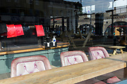As the second week of the Coronavirus lockdown continues around the capital, and the UK death toll rising by 563 to 2,325, with 800,000 reported cases of Covid-19 worldwide, faded seats and red bar mats are seen in the window of The Railway, a closed pub opposite the railway arches at the local Overground station on Clapham High Street, all in accordance with the government's forced lockdown and closure of businesses, on 1st April 2020, in south London, England.