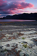 Huge clouds drift by lake Kleifarvatn and are turned red and pink by the last remaining light of the day