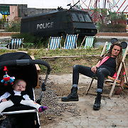 A sleepy attendant and baby in Dismaland. On the first day the show is open only a thousand locals who won free ticket gets an advanced entry to the show.Dismaland, a bemusement park set up by artist Banksy show casing more hand 40 artists. The bemusement park is set in a former lido in Weston Super-Mare.After much secrecy the show opened to a small number of locals from Weston Super-Mare Friday and fully to the public Saturday Aug 22.