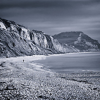 The Jurassic Coast in Dorset, England with lone male figure walking along beach in winter