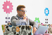 Mid-adult businessman using laptop on armchair in creative office