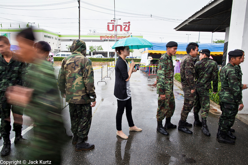 26 JUNE 2011 - CHIANG MAI, THAILAND:   A woman stands under an umbrella while she waits with a group of Royal Thai Army soldiers to cast their absentee ballots in Chiang Mai Sunday. The role of the military in this election has been fiercely debated because the Army command has indicated they would not favor a victory by Pheua Thai, the leading party in this election. Absentee voting was Sunday, July 26 in Thailand's national election. The regular voting is Sunday July 3. In Chiang Mai, center of the powerful Red Shirt opposition movement and their legal party Pheua Thai, turnout was heavy despite a steady rain. Thailand's democracy will be tested in the election, which is the most bitterly fought contest in Thai political history. The Pheua Thai represents people loyal to fugitive former Prime Minister Thaksin Shinawatra, ousted by a military coup in 2006. The ruling Democrats have governed Thailand in one form or another nearly continuously since 1932. Pre-election polls show Pheua Thai leading but not by enough to rule without forming a coalition with smaller parties.  PHOTO BY JACK KURTZ