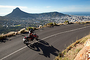 A motorcyclist rides along Table Mountain on a Ducati hypermotard 1100. Lions Head and Cape Town CBD in background. Image by Greg Beadle