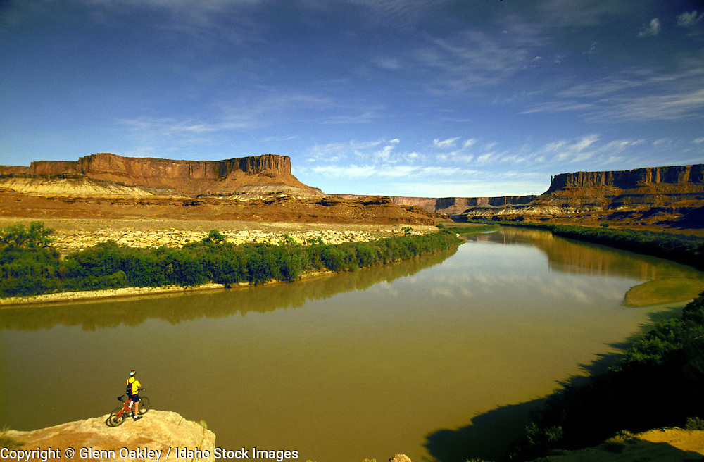 Mountain biker takes a break on a ledge to check out the Green River, White Rim Trail, Canyonlands National Park, Utah. MR