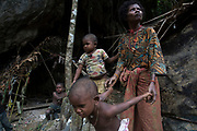 Maniq children  and Jin play in the entrance of their cave that they are currently staying in until the end of the rainy season.<br /> <br /> Evidence suggests that the Maniq, a Negrito tribe of hunters and gatherers, have inhabited the Malay Peninsula for around 25,000 years. Today a population of approximately 350 maniq remain, marooned on a forest covered mountain range in Southern Thailand. Whilst some have left their traditional life forming small villages, the majority still live the way they have for millennia, moving around the forest following food sources. <br /> <br /> Quiet and reclusive they are little known even in Thailand itself but due to rapid deforestation they are finding it harder to survive on the forest alone and are slowly being forced to move to its peripheries closer to Thai communities.