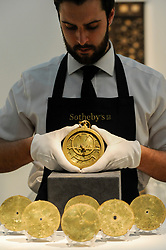 © Licensed to London News Pictures. 21/04/2017. London, UK.  A technician presents an Umayyad brass astrolabe, signed by Muhammad ibn al-Saffar, Spain, dated 1020AD, (est. GBP300-500k), at a preview at Sotheby's, New Bond Street, of upcoming sales of Arts of the Islamic World, 20th century Middle East Art and Orientalist art. Photo credit : Stephen Chung/LNP