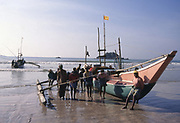 Sri Lanka. Weligama Bay - South Coast. Fisherman taking a boat out to sea in the morning.