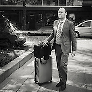 Business man dressed in suits and tie walking in central Bergen with suitcase and baggage