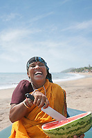 Cheerfulness mature Indian woman cutting watermelon at Vagator Beach