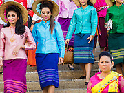 """14 JANUARY 2015 - BANGKOK, THAILAND:  Women walk to the start of the 2015 Discover Thainess parade. The Tourism Authority of Thailand (TAT) sponsored the opening ceremony of the """"2015 Discover Thainess"""" Campaign with a 3.5-kilometre parade through central Bangkok. The parade featured cultural shows from several parts of Thailand. Part of the """"2015 Discover Thainess"""" campaign is a showcase of Thailand's culture and natural heritage and is divided into five categories that match the major regions of Thailand – Central Region, North, Northeast, East and South.    PHOTO BY JACK KURTZ"""