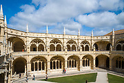 Tourists pass stone pillars and cloisters of famous Monastery of Jeronimos - Mosteiro  dos Jeronimos in Lisbon, Portugal