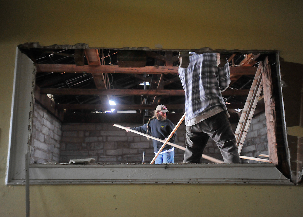 Thomas Dixon, left, and Jacob Baumgardner are scen through a whole in the wall as they remove damaged wood at The Old Crawford Depot during the renovation process on Wednesday, Oct. 20, 2010 in Crawford, Ga.