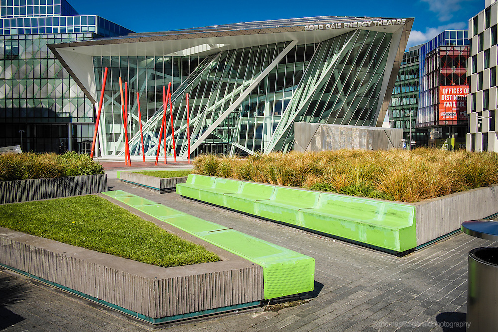 Luminous green benches contrast against the red poles and glass face of the Bord Gáis Energy Theatre in dublin's Docklands District
