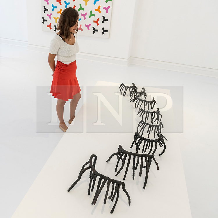 "© Licensed to London News Pictures. 25/06/2018. LONDON, UK. A staff member views an artwork by Rosemarie Castoro.  Preview of ""Lands of Lads, Land of Lashes"", an exhibition of sculptures and paintings by three female artists of the1960s and 1970s - Rosemarie Castoro, Wanda Czelkowska and Lydia Okumura - specialising in Minimal and Post-Minimal art.  The exhibition, held at Galerie Thaddaeus Ropac in Mayfair, runs 25 June to 11 August 2018.  Photo credit: Stephen Chung/LNP"